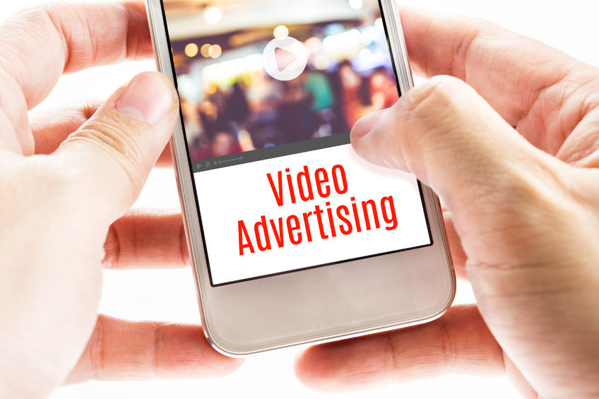 43869506 - close up two hand holding mobile with video advertising word, digital business concept.