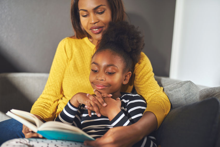 54383996 - black mom and daughter reading a book sitting on sofa smiling